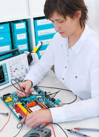 Senior female tech repairs electronic equipment