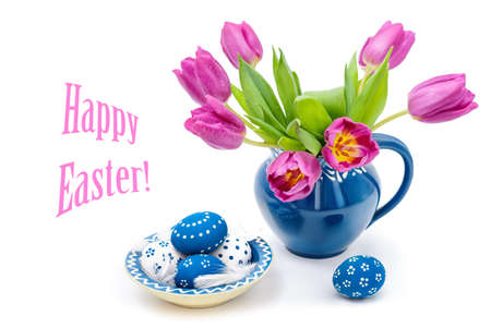 Blie ceramic vase with tulips and matching plate with painted Easter Eggs on white background photo