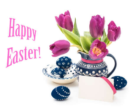 Blie ceramic vase with tulips and matching plate with painted Easter Eggs on white background, text space photo