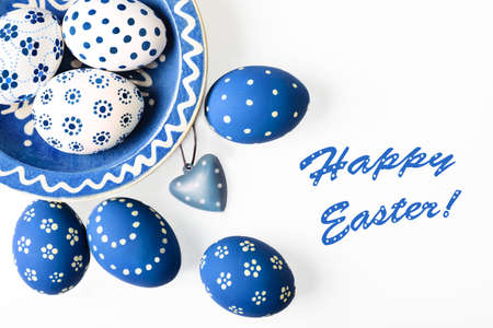 Ester eggs painter blue and white on white background, space