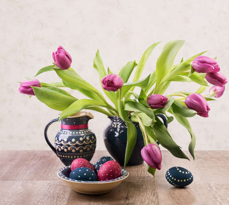 Bunch of tulips and painted Easter Eggs on a table photo