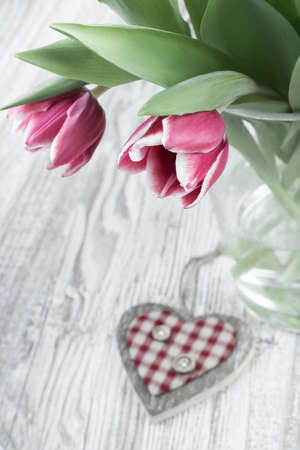 Pink stripy tulips in glass vase and wooden heart on table top, text space photo