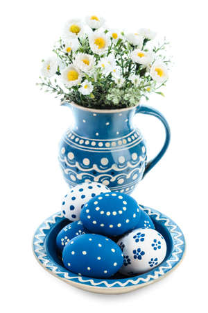 Blue ceramic plate with painted Easter Eggs and flowers in matching vase on white background photo