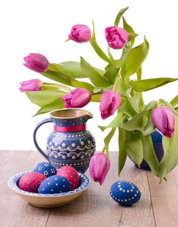 Blie ceramics with tulips and painted Easter Eggs on white background photo