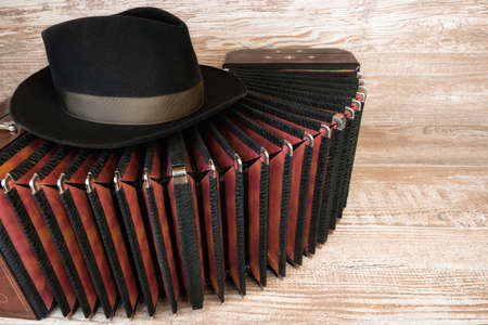 tango: Bandoneon on wooden with a male black hat on top, text space