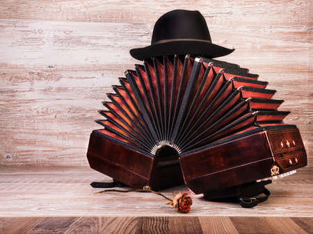 milonga: Bandoneon on wooden with a male black hat on top, text space