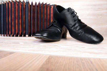 bandoneon: Pair of male dancing schoes and bandoneon on wood  Stock Photo
