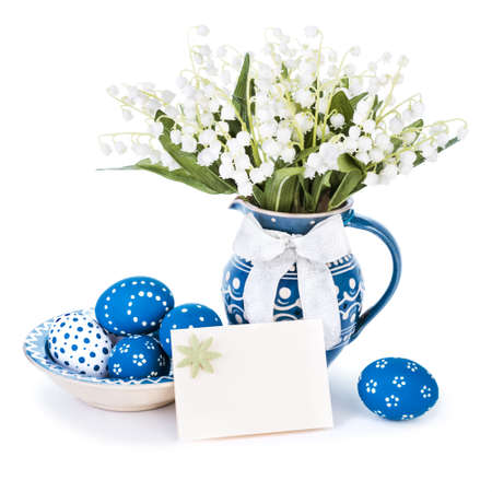 Easter eggs painted blue and spring flowers in matching vase on white   photo