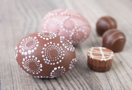 Easter eggs and chocolate pralines on wooden table