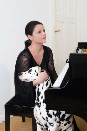 Young woman with dalmatian dog sitting by by grand piano  photo