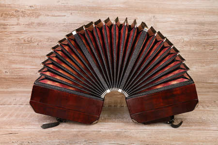 milonga: Open bandoneon on wood background