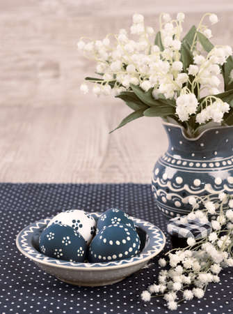 Blue and white Easter eggs and spring flowers on wooden background, text space photo