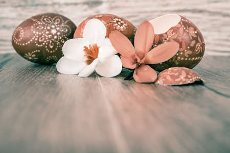 Easter eggs on wooden table, text space, shallow DOF, focus on white flower photo