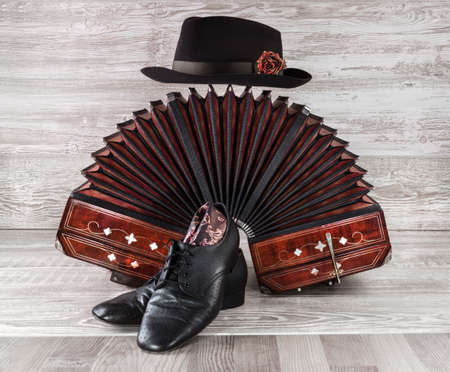 Bandoneon, pair of tango shoes and a black hat on wooden background