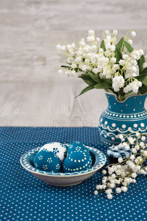 Blue ceramic plate with painted Easter Eggs and flowerson wooden table, text space photo