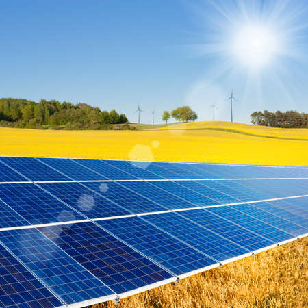Solar power cells, rapeseed field and windmills on the horizon  Stock Photo