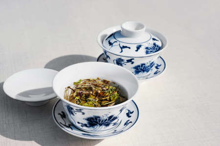 oriental medicine: Two cups of traditional white chinese tea with white peony on white table, text space