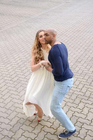 cuban women: A couple dancing salsa outdoors, text space