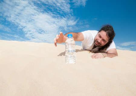 のどが渇いた男に砂漠では水のボトルのために達する