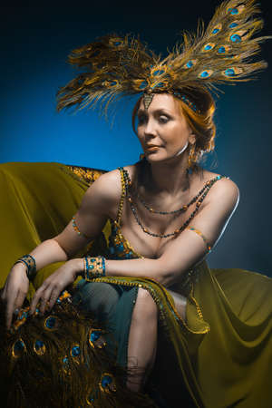 Dancer in exotic costume sits in armchair on dark background photo