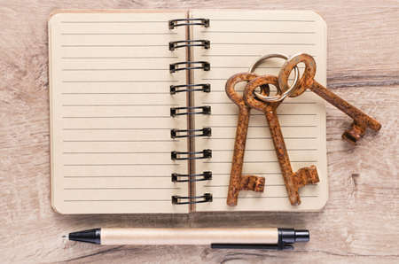 locked: Open notebook, a pen and a bunch of old keys on wooden table, text space Stock Photo