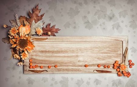 Wooden board with Autumn decorations on natural background, toned image, copy space photo