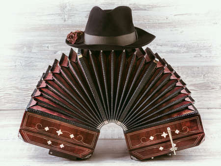 Bandoneon on wooden with a male black hat on top, text space