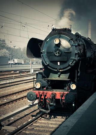 railtrack: Historical German steam locomotive by the station platform, toned image