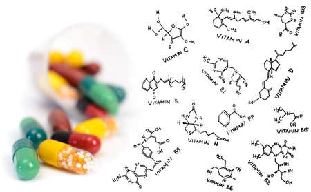 enzymes: High potency vitamin supplement pills and chemical formulae of vitamins Stock Photo