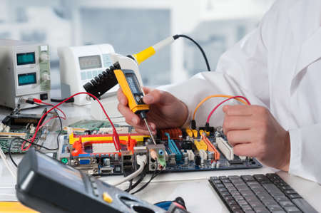 ingenieria el�ctrica: Reparador fija de equipos electr�nicos en el centro de servicio Foto de archivo