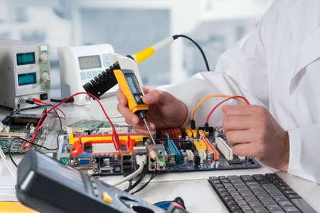 Reparateur repareert elektronische apparatuur in het service center