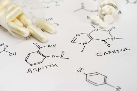 Aspirin in capsules and caffein in tablets on paper with their chemical formula