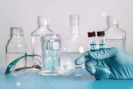 nitril: Two liquid samples in plastic vials in the hand of female scientist