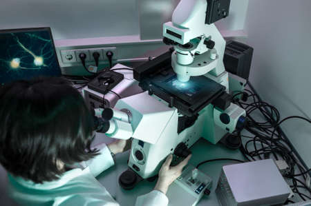 Young oriental scientist works with modern inverted microscope  photo