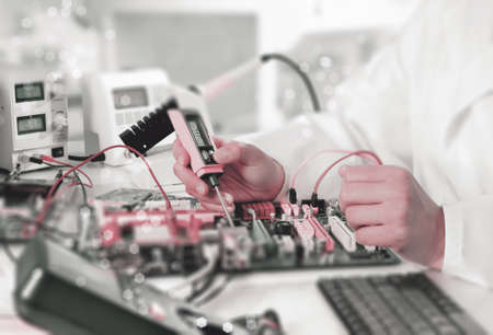 electrical engineering: Repairman fixes electronic equipment in service center, tiltßshift effect, space for your text