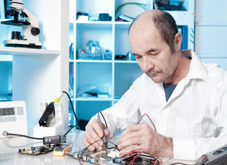 technical service: Senior male tech tests electronic equipment