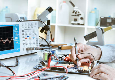 Electronics repair service, hands of senior tech reparing an electronic circuit Stockfoto