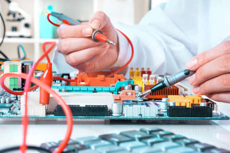 faulty: Electronics repair service, hands of female tech reparing an electronic circuit Stock Photo