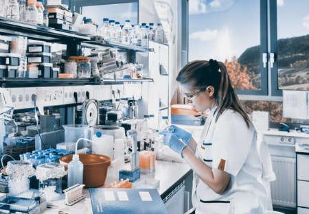 bata de laboratorio: El científico joven trabaja en el laboratorio biológico moderno, imagen de tonos