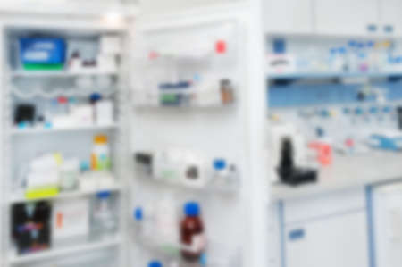 cold storage: Scientific background: open fridge with reagensts and laboratory interior out of focus Stock Photo