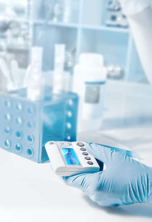 nitril: Scientific background with gloved hand holding electronic timer as a focal point, tilt-shift effect,  text space Stock Photo