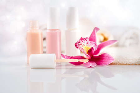 nail varnish: Wellness and body care background. Nail varnish, towels and a single orchid flower Stock Photo