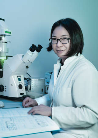 Young oriental scientist works with modern fluorescent microscope photo