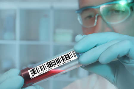 clinical trial: Tech with a medical sample labeled with a barcode