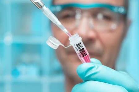 clinical trial: Scientist or tech holds liquid biological sample in gloved hands Stock Photo