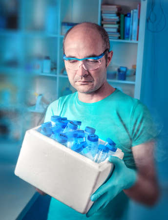 nitril: Senior scientist with medical or biological samples in white ice box Stock Photo