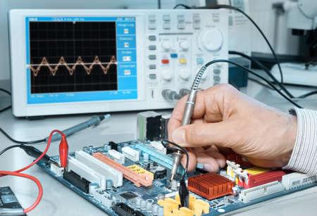 Elektronica reparatie service, handen van senior tech reparing een elektronische schakeling Stockfoto