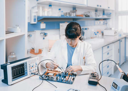 white coats: Young scientist repairs electronic device in modern laboratory Stock Photo