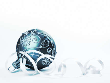 Blue-green Christmas bauble on white surface, space photo