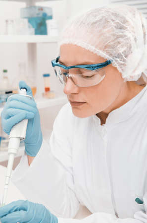 technical assistant: Young female tech or scientist works with automatic pipette Stock Photo